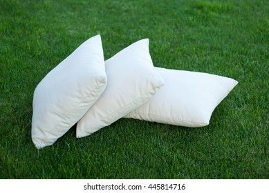 Three pillows on the cosy green grass