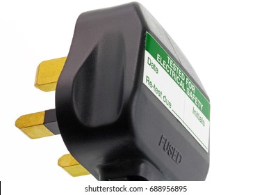 Three pin plug – An isolated UK plug on a white background  with a portable appliance testing sticker on it