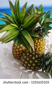 Three pineapples in a white flower shaped metal bowl.