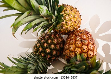 Three pineapples in a white flower-shaped metal fruit bowl.
