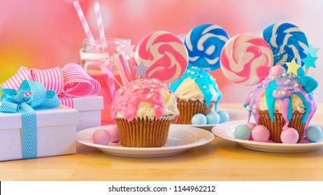 Three pink and blue theme colorful novelty cupcakes decorated with candy and large heart shaped lollipops for children's, teen's birthday or holiday celebrations.