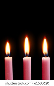 Three pink candles alight with black background