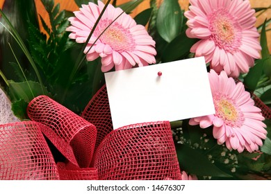 Three pink gerbera flowers with blank gift tag