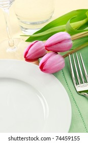 Three pink tulips grace a table setting in fresh Spring colors making a perfect background for Easter or Mother's Day promotions - ample copy space provided with the empty white plate