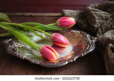 Three pink tulips on a silver tray sits on a dark wood table.