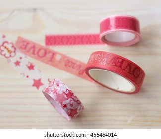 Three pink washi tape rolls on white wooden table. Sticky adhesive tape with iamges.