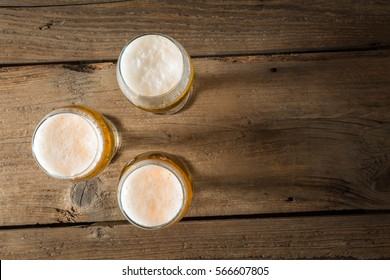 Three pints of beer on a wooden table. top view