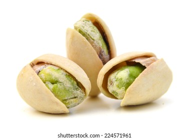 Three pistachios close up. Isolated on a white background.