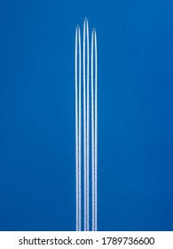 Three planes in formation in the blue sky with a condensation trails