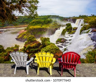 Three plastic armchairs - chaise longue - white, yellow, red - set at waterfalls. Scenic basaltic rock formations famous waterfalls Iguazu Falls. The concept of ecological and phototourism