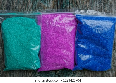 three plastic bags with colored sand on the table
