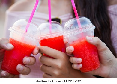 Three plastic cups with an icy red drink held by three hands
