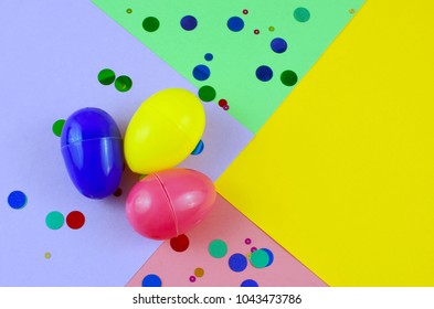 Three plastic easter eggs in blue, green, yellow and pink, with confetti on a geometric mutli-colored background made of rough textured paper. Studio lighting is reflected in eggs.