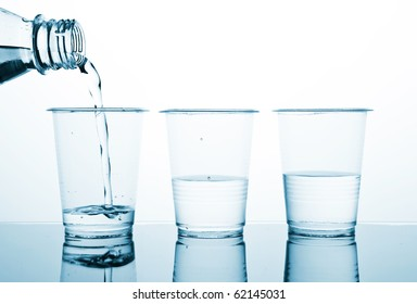 Three plastic glasses with water. The water following from a bottleneck in a glass. Blue-White duotone image.