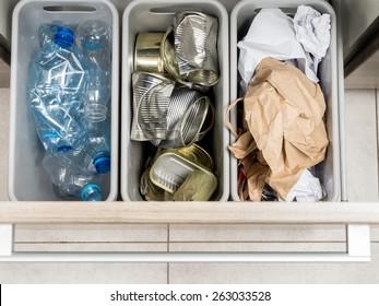 Drei Kunststoffabfälle in Küchentischkabine mit getrennten Haushaltsabfällen - PET-Flaschen, Papier- und Metalldosen, die von oben aufgenommen wurden