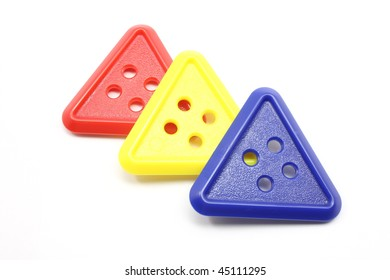 Three plastic triangle buttons, red, yellow, and blue.