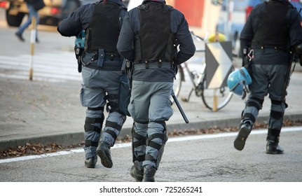 three police officers with bulletproof vests riot in uniform patrolling the streets of the city during the anti-terrorism controls