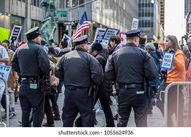 Three policemen watch protestors with signs walking in a March For Our Lives rally at New York City on March 24th 2018.