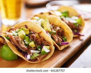 three  pork carnitas street tacos in yellow corn tortilla with avocado, onion, cilantro and cabbage