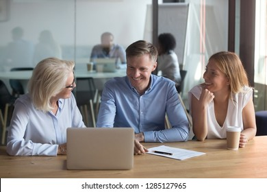 Three positive employees sitting in coworking space working together discussing project planning stages of cooperation, take a break telling jokes smiling feels satisfied having pleasant conversation