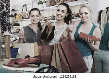 three positive european girls holding a paper shopping bags in the boutique