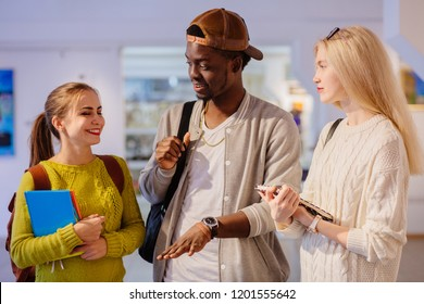 Three positive, friendly nice look students talking, sharing news indoor in art gallery.Hipster black man and two european women spending time together. Multi ethnic, study abroad, friendship concept.