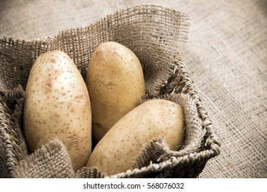 Three Potatoes on burlap basket.