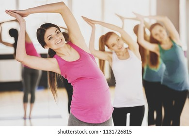 Three Pregnant Women Doing Exercises on Mats in Gym on Wooden Floor. Healthy Lifestyle. Indoor Sports and Fitness. Pregnancy and Motherhood Concepts. Mother Expecting Baby Concept.