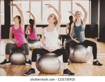 Three Pregnant Women Doing Exercises on Balls in Gym on Wooden Floor. Healthy Lifestyle. Indoor Sports and Fitness. Pregnancy and Motherhood Concept. Mother Expecting Baby Concept.