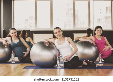 Three Pregnant Women Doing Exercises with Balls in Gym on Wooden Floor. Healthy Lifestyle. Indoor Sports and Fitness. Pregnancy and Motherhood Concept. Mother Expecting Baby Concept.
