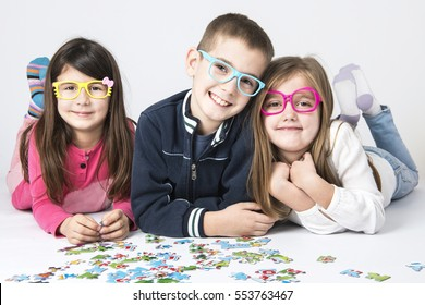 three preschool kids playing with puzzles