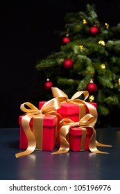 Three presents with gold ribbon in an elegant Christmas setting