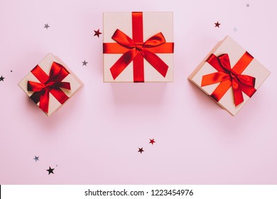 Three presents with red bow on pastel trendy pink background with little silver sparkles. Flat lay style.