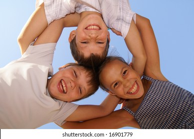 Three preteen friends enjoying summer outdoors on blue sky background