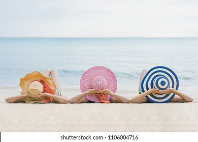 Three pretty beautiful asian women wearing colourful swimwear bikini with hat having fun and relax sunbathing on the beach in the summer, travel holidays concept