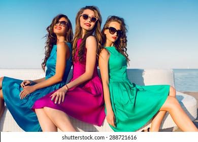 3b83b731eae Three pretty friends in same colorful dresses posing near the beach