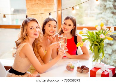 Three pretty, nice, confident, successful girls sitting in restaurant, holding with hands, clinking glasses with champagne, wine, alcohol, beverage, looking at camera