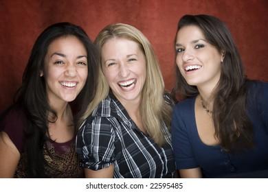 Three pretty women laughing in a studio setting