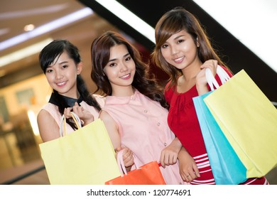 Three pretty women with shopping bags looking at camera