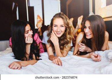 Three Pretty   young friends chatting on bed at home in the  cozy  bedroom.