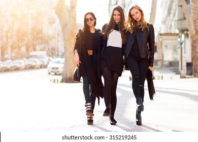 Three pretty  young girls having fun outdoors together . Lifestyle urban mood.  Center city background. Best friends wearing black casual outfit.