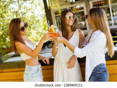 Three pretty young women drinking coctais and having fun in the beach bar