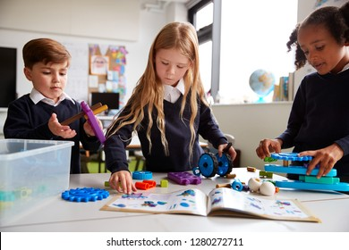 Three primary school children  working together, following an instruction book and using construction blocks in a classroom, front view, close up