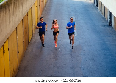 Three professional athletes jogging down the alleyway between garages