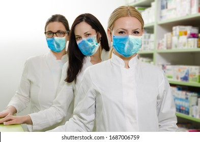 Three professional female pharmacists with masks standing in row
