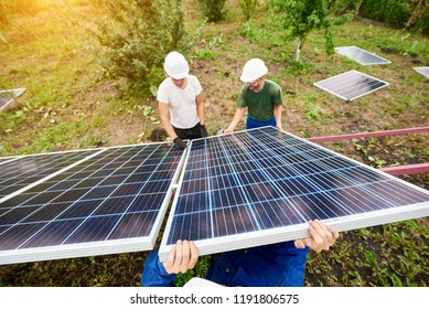 Three professional technicians connecting solar photo voltaic panel to metal platform using screwdriver on green summer background, side view. Stand-alone exterior solar panel system installation.