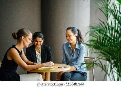 Three professional women of varying ethnicities sit and have a meeting discussion around a table in a meeting room during the day. One is an Indian Asian woman, the other Chinese and the last White.