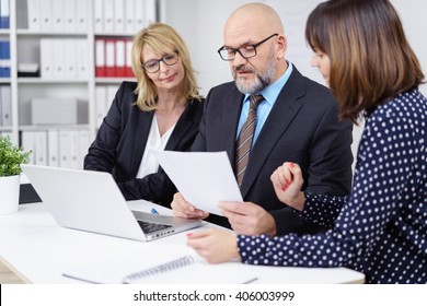 Three professional workers meeting and discussing something important while seated at white table with laptop computer