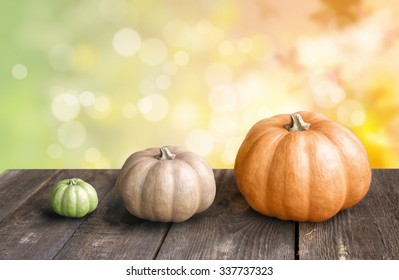 Three pumpkins of different degrees of maturity on wooden table with bokeh background. The concept