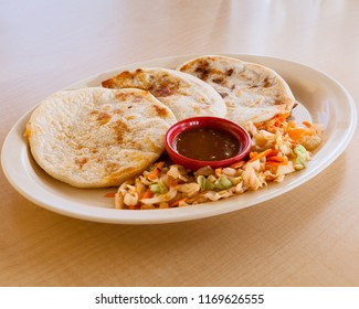 Three pupusas served with a side of grilled veggies.